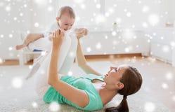 在家使用与婴孩的愉快的母亲 免版税库存图片