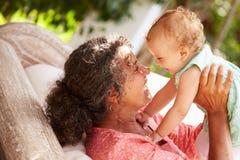 在家使用与孙女的祖母在庭院里 免版税库存图片