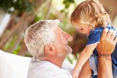在家使用与孙子的祖父在庭院里 库存照片