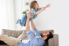 在家使用与小儿子的愉快的年轻父亲 免版税库存图片