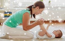 在家使用与小婴孩的愉快的母亲 免版税库存照片