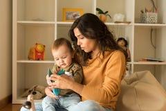 在家使用与小孩的母亲 图库摄影