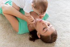 在家使用与小婴孩的愉快的母亲 图库摄影