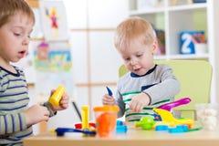 在家使用与彩色塑泥或日托中心的愉快的孩子 免版税库存图片