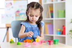 在家使用与彩色塑泥的孩子女孩 免版税图库摄影