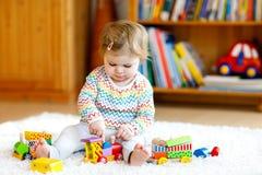 在家使用与教育木玩具或托儿所的可爱的逗人喜爱的美丽的矮小的女婴 有五颜六色的小孩 库存照片