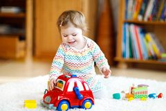 在家使用与教育木玩具或托儿所的可爱的逗人喜爱的美丽的矮小的女婴 有五颜六色的小孩 免版税图库摄影