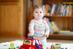 在家使用与教育木玩具或托儿所的可爱的逗人喜爱的美丽的矮小的女婴 有五颜六色的小孩 图库摄影