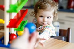 在家使用与教育玩具或托儿所的可爱的逗人喜爱的美丽的矮小的女婴 图库摄影