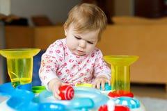 在家使用与教育玩具或托儿所的可爱的逗人喜爱的美丽的矮小的女婴 免版税库存图片