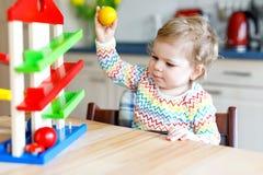 在家使用与教育玩具或托儿所的可爱的逗人喜爱的美丽的矮小的女婴 免版税库存照片