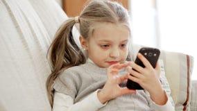 在家使用与智能手机的逗人喜爱的小女孩
