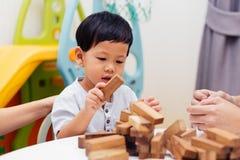 在家使用与木块的亚裔孩子在屋子里 一幼儿园和幼儿园孩子的教育玩具 免版税库存照片