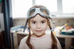 在家使用与杯的小女孩飞行员 免版税库存图片