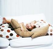 在家使用与枕头的小逗人喜爱的白肤金发的女孩 免版税图库摄影