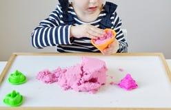 在家使用与桃红色运动沙子的小白种人女孩 库存照片
