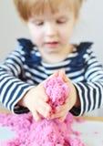 在家使用与桃红色运动沙子的小白种人女孩 图库摄影