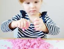 在家使用与桃红色运动沙子的小白种人女孩 免版税库存图片