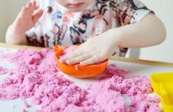 在家使用与桃红色运动沙子的小白种人女孩 免版税图库摄影
