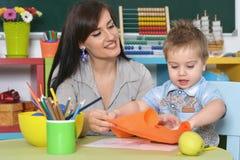 在家使用与母亲或幼儿园的小男孩 库存图片