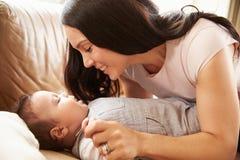在家使用与沙发的愉快的男婴的母亲 免版税库存照片