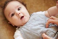在家使用与沙发的愉快的男婴的母亲 库存图片