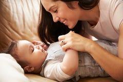 在家使用与沙发的愉快的男婴的母亲 图库摄影