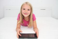 在家使用与片剂、膝上型计算机和电话的小孩 库存照片
