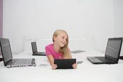 在家使用与片剂、膝上型计算机和电话的小孩 免版税库存图片
