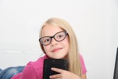 在家使用与片剂、膝上型计算机和电话的小孩 免版税图库摄影