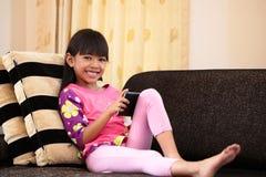 在家使用与片剂的亚裔小女孩 图库摄影