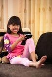 在家使用与片剂的亚裔小女孩 免版税库存图片