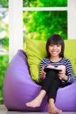 在家使用与片剂计算机的小亚裔女孩在家 库存图片