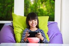 在家使用与片剂计算机的小亚裔女孩在家 免版税库存照片