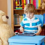 在家使用与片剂计算机的小孩男孩在他的屋子里 免版税库存图片