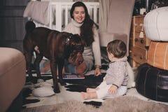 在家使用与狗的愉快的家庭 母亲和吃曲奇饼的男婴 免版税库存照片