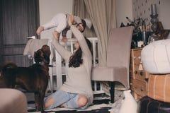 在家使用与狗的愉快的家庭 母亲和吃曲奇饼的男婴 库存图片