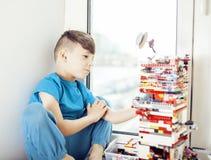 在家使用与玩具愉快微笑,生活方式儿童概念的小逗人喜爱的学龄前儿童男孩 免版税库存图片