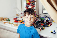 在家使用与玩具愉快的smil的小逗人喜爱的学龄前儿童男孩 免版税库存图片