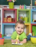 在家使用与玩具或幼儿园的小男孩 免版税库存图片