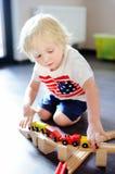 在家使用与玩具木火车的逗人喜爱的小孩男孩 库存照片