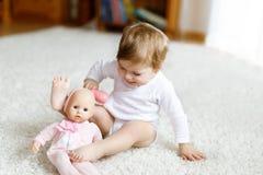 在家使用与玩具玩偶或托儿所的可爱的逗人喜爱的美丽的矮小的女婴 免版税库存图片