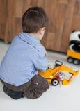 在家使用与玩具的一个小男孩的背面图 免版税库存图片