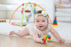 在家使用与玩具的小女孩在地板上 免版税库存照片
