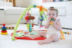 在家使用与玩具的小女孩在地板上 图库摄影
