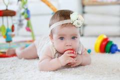 在家使用与玩具的小女孩在地板上 库存照片