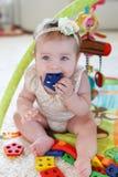 在家使用与玩具的小女孩在地板上 库存图片