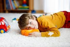 在家使用与玩具的小白肤金发的孩子男孩特写镜头画象  便衣的愉快的微笑的孩子 免版税库存图片