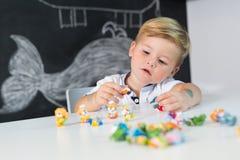 在家使用与玩具的逗人喜爱的小孩男孩画象在书桌 库存照片