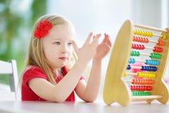 在家使用与算盘的逗人喜爱的小女孩 学会聪明的孩子计数 图库摄影